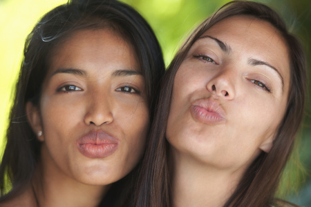 Close up portrait of two woman friends puckering lips