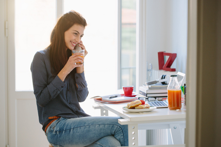 Young woman using telephone while breakfasting