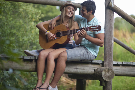 Teenage couple playing guitar and singing