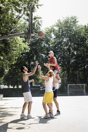 25 35: Group of friends having fun playing basketball