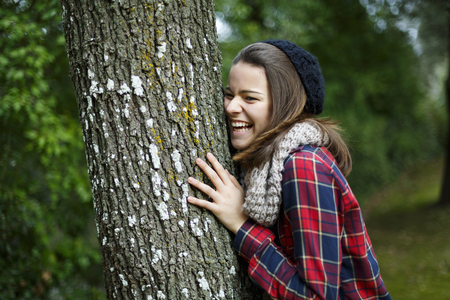Teenage girl leaning on tree in forest LANG_EVOIMAGES