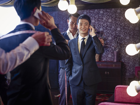 50 54 years: Young man trying on suit in traditional tailors shop