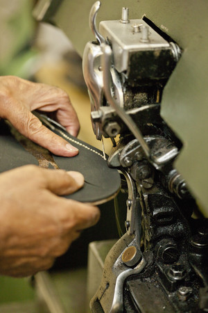 Cobbler sewing sole of boot