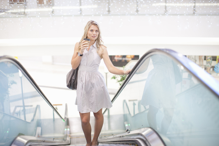 Young woman going up escalator in mall