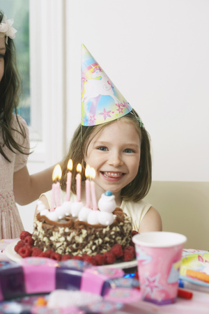 Portrait of young girl enjoying her birthday party