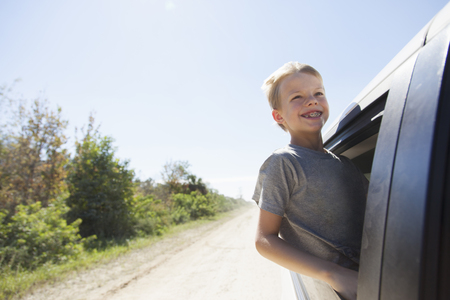 leaning on the truck: Boy having fun leaning out of truck window LANG_EVOIMAGES