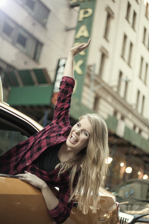 Young woman waving out from yellow cab, New York City, USA