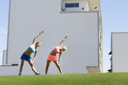 in unison: Two young female athletes stretching in park