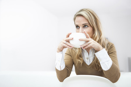 Female office worker having coffee break LANG_EVOIMAGES