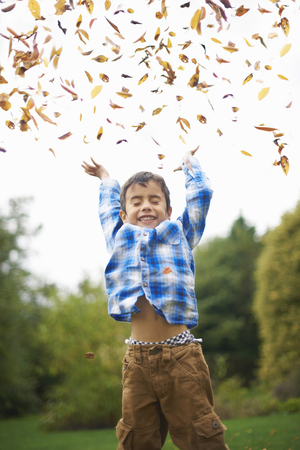 Male toddler in the garden throwing up autumn leaves