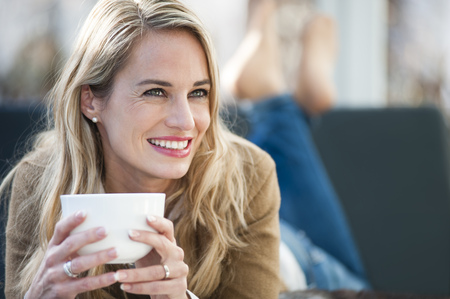people: Mid adult woman relaxing on sofa with coffee LANG_EVOIMAGES