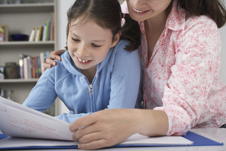 Mother helping young daughter with homework LANG_EVOIMAGES