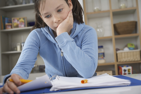 Girl sitting at kitchen counter struggling with homework