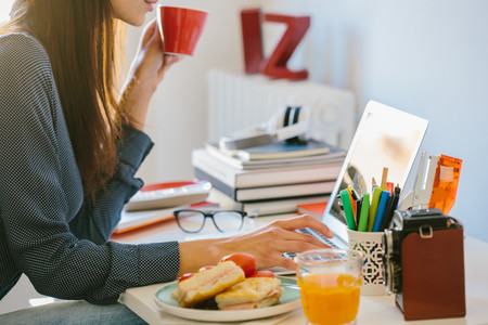 Young woman using laptop while breakfasting