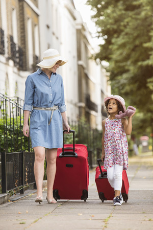 Mother and daughter pulling suitcases along pavement