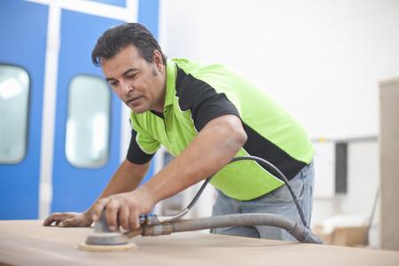Man sanding down plank of wood in carpenters workshop