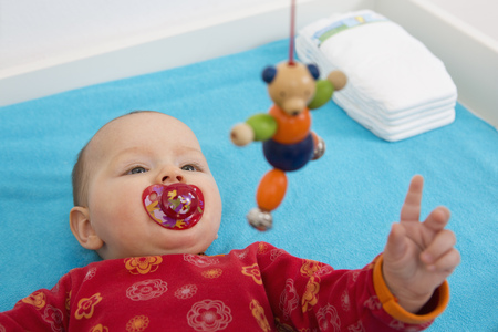 Contented 7 month old baby girl playing with dangling teddybear