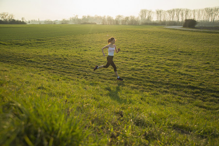 Young female runner in hilly field