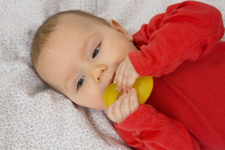 7 month old baby girl in crib with teething ring in her mouth