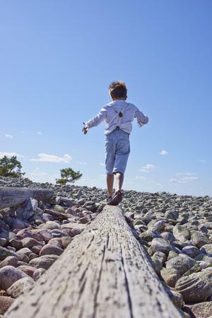 Boy balancing on log on beach LANG_EVOIMAGES