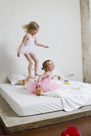niños vistiendose: Dos hermanas jóvenes vestidos como bailarines de ballet jugando en la cama