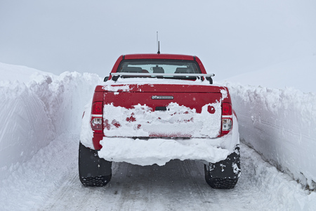 Mature woman driving red pick up truck on snow walled road, Fljotsheidi, North Iceland