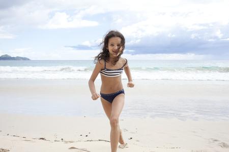 Girl running on beach in Seychelles LANG_EVOIMAGES