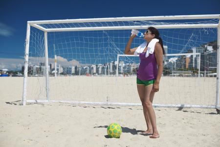 Mature woman and soccer ball on Copacabana beach, Rio De Janeiro, Brazil