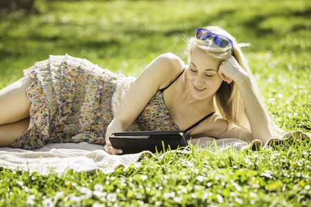Young woman lying in forest looking at digital tablet
