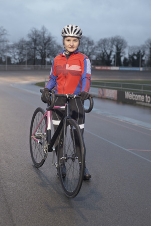 Portrait of  young female cyclist with cycle at velodrome