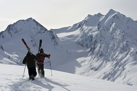 skiers: Two mid adult male skiers walking uphill, Obergurgl, Austria LANG_EVOIMAGES