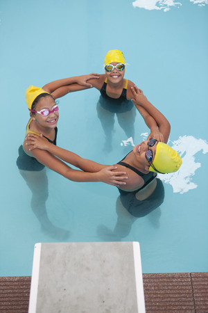 Portrait of three schoolgirl swimmers making circle LANG_EVOIMAGES
