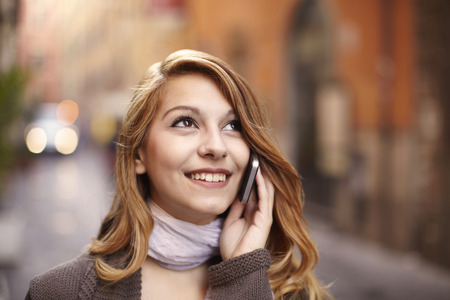 Young woman chatting on smartphone on Rome street, Italy LANG_EVOIMAGES