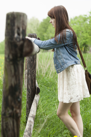 Young woman leaning on wooden fence LANG_EVOIMAGES
