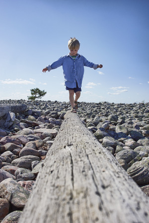 Boy balancing on log on beach LANG_EVOIMAGES
