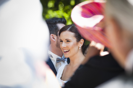 Mid adult bride and groom surrounded by guests LANG_EVOIMAGES