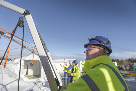 Emergency Response Team workers erecting tent control centre LANG_EVOIMAGES