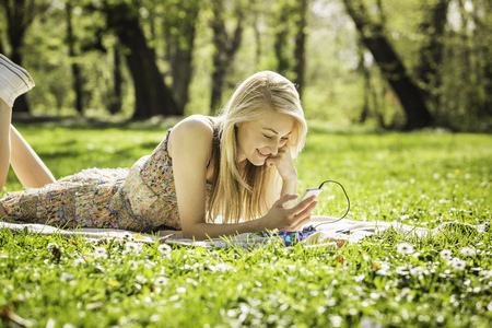 Young woman lying in forest looking at smartphone LANG_EVOIMAGES
