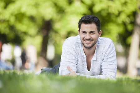 Portrait of smiling young man lying in park