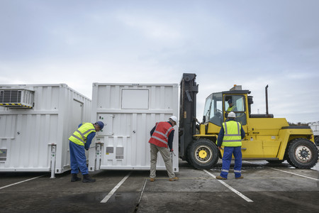 emergency vest: Emergency Response Team workers installing emergency control rooms with fork lift truck