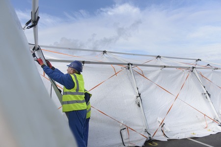 emergency vest: Emergency Response Team workers erecting tent control centre LANG_EVOIMAGES