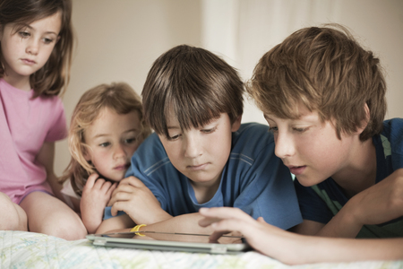 7 8: Brothers and sisters lying on bed looking at digital tablet