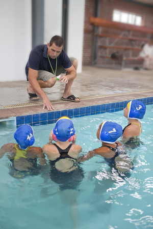Four schoolgirl water polo players listening to teacher poolside LANG_EVOIMAGES