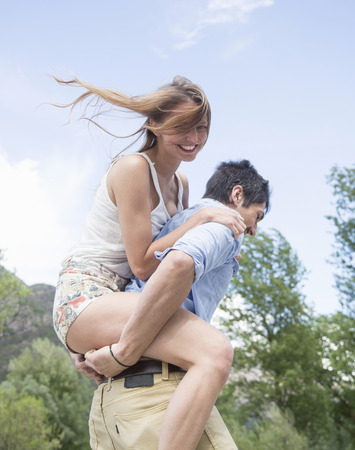 Young man giving girlfriend piggy back ride