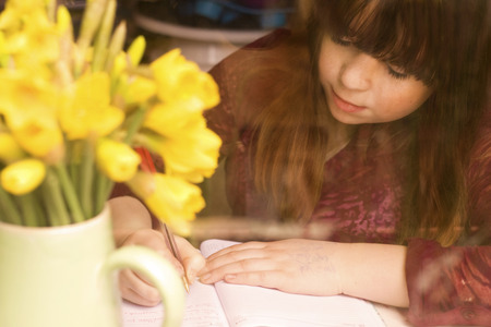 Girl writing by daffodils on desk