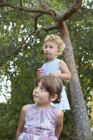 Candid portrait of two young sisters looking up
