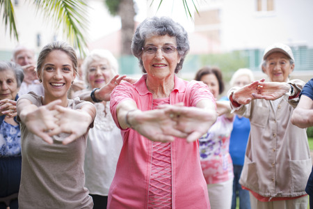 65 69 years: Medium group of seniors exercising in retirement villa garden
