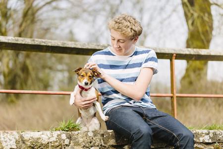 Teenage boy sitting on footbridge with his jack russell dog