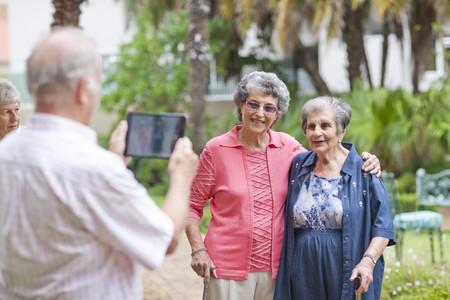 75 80: Senior man photographing friends in retirement villa garden