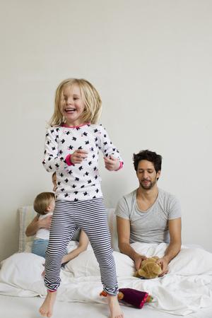 Young girl jumping on her parents bed LANG_EVOIMAGES